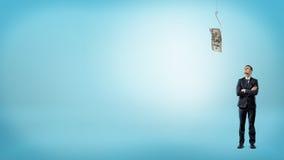 Малый предприниматель с его руками пересек смотреть вверх на долларовую банкноту зацеплянную удя крюк Стоковая Фотография