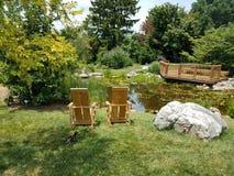 Малый пруд с стульями, валуном, деревянной платформой замечания и утками Стоковая Фотография RF