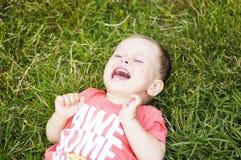 Малый плача мальчик на траве Стоковое фото RF