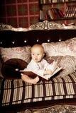 Малый ребенок в внутреннем чтении книга Усмехаясь младенец в Стоковое Фото