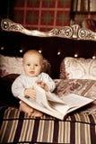 Малый ребенок в внутреннем чтении книга Усмехаясь младенец в Стоковое Изображение