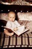 Малый ребенок в внутреннем чтении книга Усмехаясь младенец в Стоковые Изображения RF