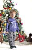Малый ребенок о рождественской елке держит красную лампу с рюкзаком Стоковые Изображения RF