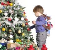 Малый ребенок о рождественской елке с 2 красными лампами с рюкзаком Стоковые Изображения