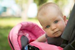 Малый ребенок смотря вверх пока сидящ в pram Стоковые Изображения