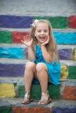 Малый счастливый ребёнок в голубом платье на красочных лестницах Стоковые Изображения