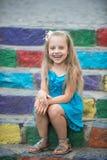 Малый счастливый ребёнок в голубом платье на красочных лестницах Стоковое Фото