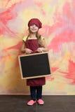 Малый счастливый шеф-повар девушки в шляпе, рисберме с классн классным Стоковая Фотография