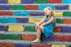Малый усмехаясь ребёнок в голубом платье на красочных лестницах Стоковая Фотография RF