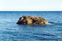 Малый утесистый остров в море Стоковые Изображения
