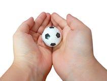 Малый футбольный мяч в обоих рука на белой предпосылке Стоковые Изображения