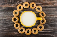 Малый хлеб звенит вокруг желтой чашки молока на таблице Стоковое Фото