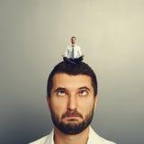 Малый человек отдыхая на большом головном человеке Стоковые Фотографии RF