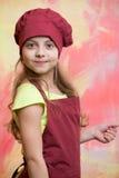 Малый шеф-повар девушки с счастливой стороной в шляпе и рисберме Стоковая Фотография RF