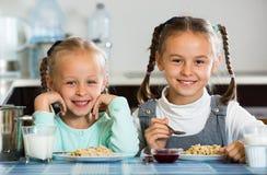 2 малых девушки есть здоровую овсяную кашу Стоковая Фотография RF