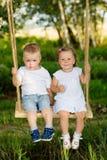 2 малых дет едут на качании outdoors Стоковые Изображения