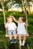 2 малых дет едут на качании outdoors Стоковое Фото