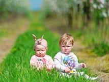 2 малых дет сидят в зеленой траве Стоковое фото RF