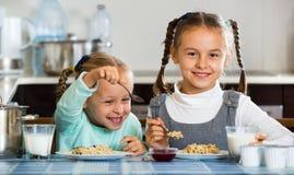 2 малых жизнерадостных девушки есть здоровую овсяную кашу Стоковое Фото