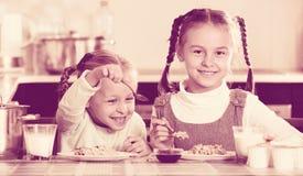 2 малых жизнерадостных девушки есть здоровую овсяную кашу Стоковая Фотография