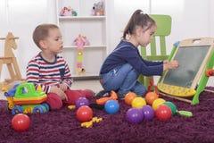 Малыши играя в комнате стоковые фото
