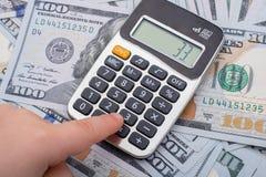 Малыш держит калькулятор на банкнотах долларов США Стоковое Изображение