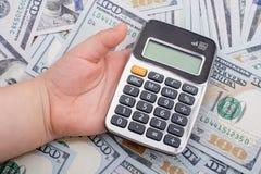 Малыш держит калькулятор на банкнотах долларов США Стоковое Фото
