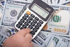 Малыш держит калькулятор на банкнотах долларов США Стоковые Фото