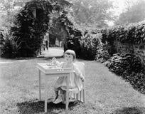 Малыш есть на таблице в саде (все показанные люди более длинные живущие и никакое имущество не существует Гарантии поставщика кот Стоковые Фотографии RF