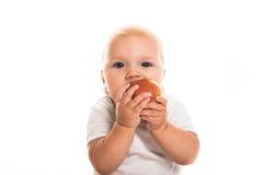 Малыш есть яблоко на белой предпосылке Стоковая Фотография RF