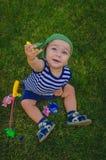 Малыш мальчика играя рыболовов сидя на свежем зеленом Ла Стоковые Фотографии RF