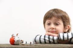 Малыш наблюдая, как миниатюрные люди сломали яичко стоковое изображение