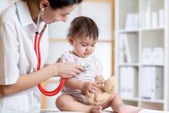 Малыш ребенка женского доктора рассматривая с стетоскопом Стоковое Изображение RF