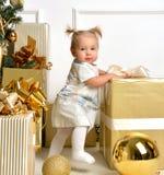 Малыш ребенка младенца рождества около рождественской елки золота представляет a Стоковые Изображения