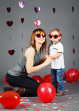 Малыш ребёнка с матерью в студии нося смеяться над смешных стекел усмехаясь имеющ потеху Стоковые Изображения