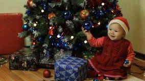 Малыш smilling рядом с рождественской елкой сток-видео