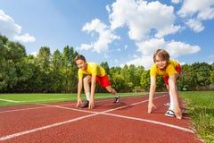 2 мальчика в готовом положении для того чтобы побежать марафон стоковая фотография rf