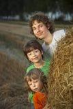 3 мальчика в стоге сена в поле стоковое изображение