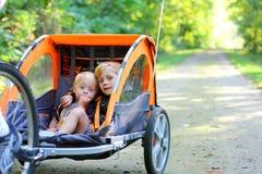 2 мальчика в трейлере велосипеда снаружи Стоковое фото RF