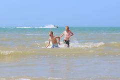 2 мальчика имея потеху в море Стоковые Фото