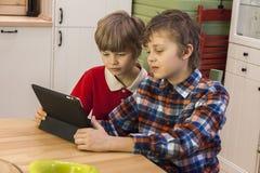 2 мальчика используя беспроволочную таблетку Стоковые Фото
