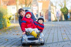 2 мальчика и отец маленьких ребеят играя с автомобилем, outdoors Стоковая Фотография