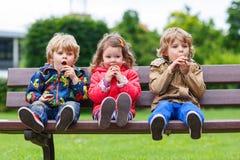 2 мальчика и одна девушка есть шоколад стоковые фото