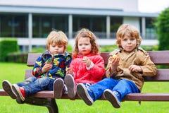 2 мальчика и одна девушка есть шоколад Стоковое Фото