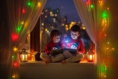 2 мальчика, книга чтения на окне Стоковая Фотография