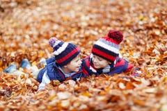 2 мальчика маленького ребенка лежа в листьях осени, внутри Стоковое фото RF