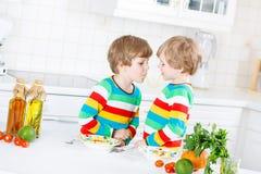 2 мальчика маленького ребенка есть спагетти в отечественной кухне Стоковое Изображение RF