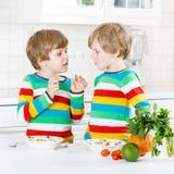 2 мальчика маленького ребенка есть спагетти в отечественной кухне Стоковая Фотография