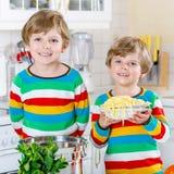 2 мальчика маленького ребенка есть спагетти в отечественной кухне Стоковые Фотографии RF