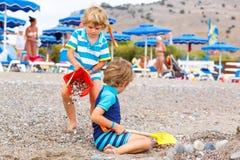 2 мальчика маленького ребенка играя на пляже с камнями Стоковое Изображение RF